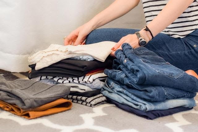 A person decluttering and going through their clothes